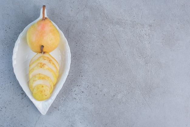 Um prato chique com pêra servindo sobre fundo de mármore.