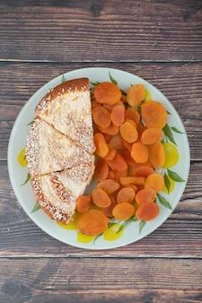 Um prato colorido com damascos secos e pedaços de tortas deliciosas.