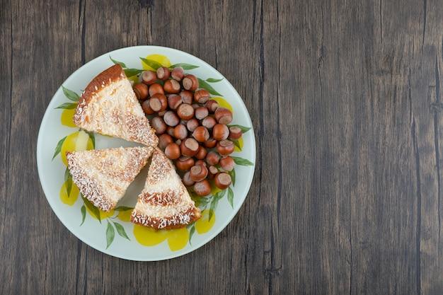 Um prato colorido com pedaços de deliciosas tortas e castanhas.