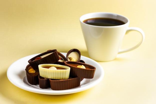 Um prato com chocolates e uma xícara de café em um fundo amarelo