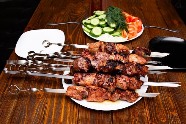 Um prato com churrasqueira kebab de carne frita no fogo, amarrada em varas de metal, ao lado de um prato com legumes para o prato pronto.