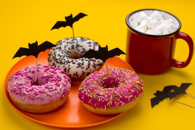 Um prato com donuts decorados com morcegos cortados em papel e uma caneca de cacau com marshmallows na mesa em uma festa de halloween