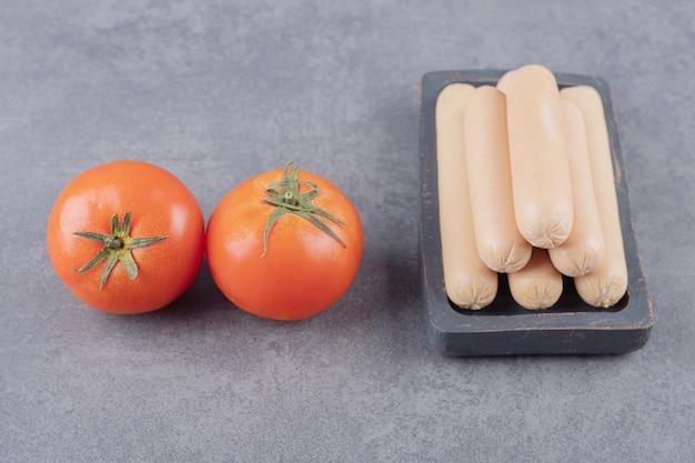 Um prato com linguiça cozida e tomate vermelho