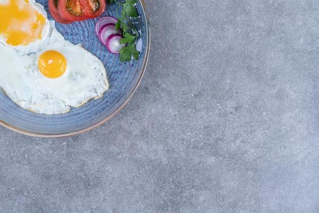 Um prato com ovos fritos e vegetais fatiados. foto de alta qualidade