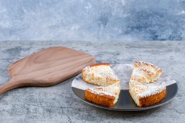 Um prato com pedaços de bolo delicioso sobre uma mesa de mármore.