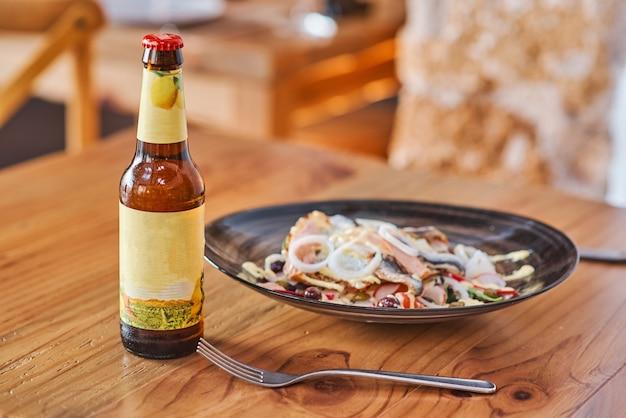 Um prato com peixe arenque e uma garrafa de cerveja numa mesa de madeira