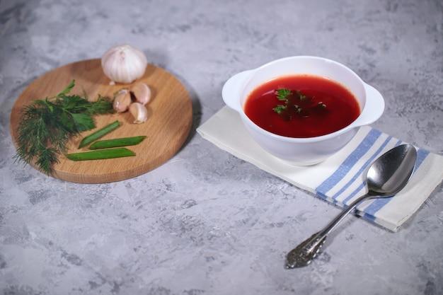 Um prato com sopa de beterraba em cima da mesa, ao lado do tabuleiro, é salsa, endro, cebola verde e alho. almoço saboroso e saudável.