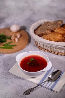 Um prato com sopa de beterraba em cima da mesa, ao lado do tabuleiro, é salsa, endro, cebola verde e alho e uma cesta com pão. almoço saboroso e saudável.