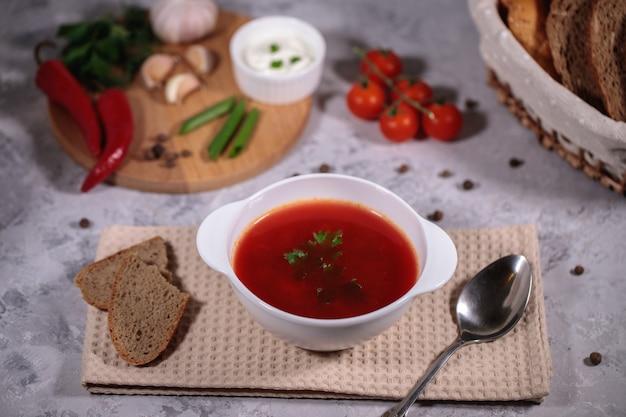 Um prato com sopa de beterraba em cima da mesa, ao lado do tabuleiro são legumes