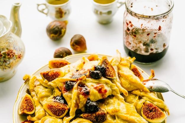 Um prato com tortas e figos na mesa, utensílios de cozinha, uma jarra aberta de geléia, um jogo de chá