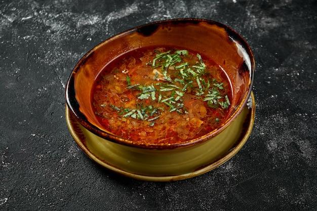 Um prato da cozinha georgiana - kharcho, sopa de carne com arroz, nozes e tklapi ou molho azedo tkemali. sopa picante em mesa escura