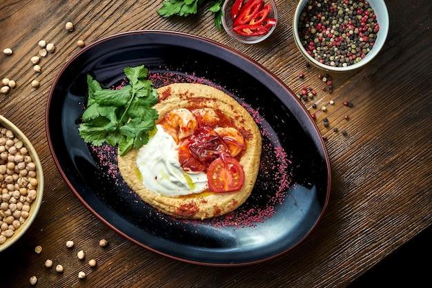 Um prato de aperitivo oriental clássico - hummus de grão de bico com molho branco, cebola caramelizada, iogurte branco e camarão, servido em um prato preto sobre uma mesa de madeira. comida de restaurante