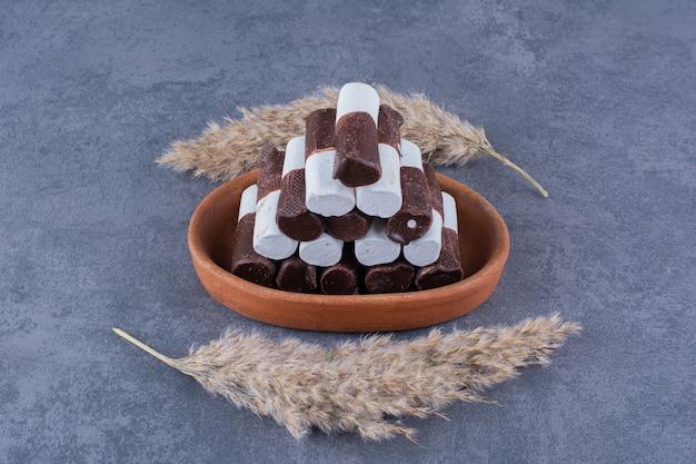 Um prato de argila com palitos doces brancos e escuros na pedra.