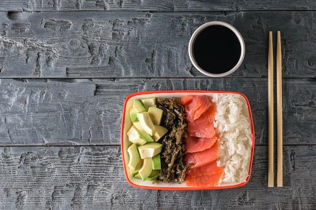 Um prato de arroz havaiano, abacate, salmão e algas e molho de soja em uma mesa de madeira preta. a vista do topo.