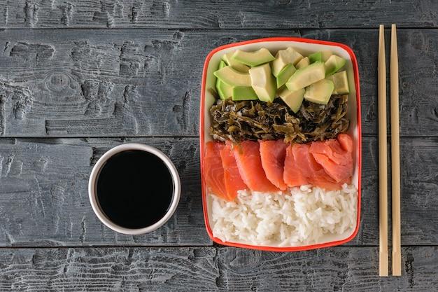 Um prato de arroz havaiano, abacate, salmão e algas e molho de soja em uma mesa escura e preta. a vista do topo.