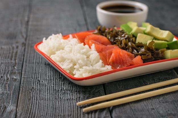 Um prato de arroz havaiano, abacate, salmão e algas e molho de soja em uma mesa preta. a vista do topo.