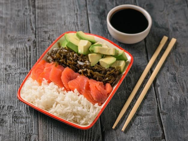 Um prato de arroz havaiano, abacate, salmão e algas e molho de soja em uma mesa rústica preta. a vista do topo.