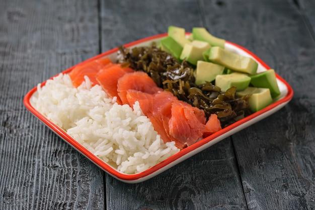 Um prato de arroz havaiano, abacate, salmão e algas sobre uma mesa rústica. a vista do topo.