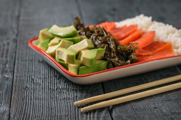 Um prato de arroz havaiano, abacate, salmão e algas sobre uma mesa rústica preta. a vista do topo.