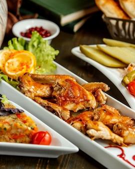 Um prato de asas de frango frito, guarnecido com suace