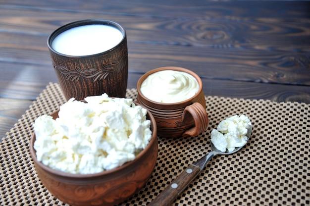 Um prato de barro com queijo cottage uma caneca de barro com creme de leite