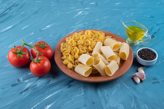 Um prato de barro de macarrão cru com óleo e tomates vermelhos frescos sobre uma superfície azul.