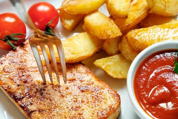 Um prato de batatas fritas com catchup, fundo de madeira