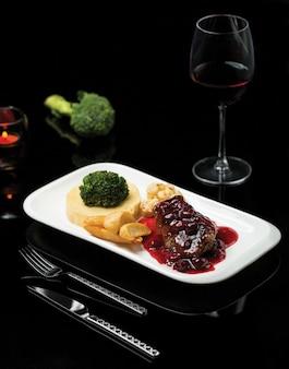 Um prato de bife em molho de vinho tinto e purê de legumes