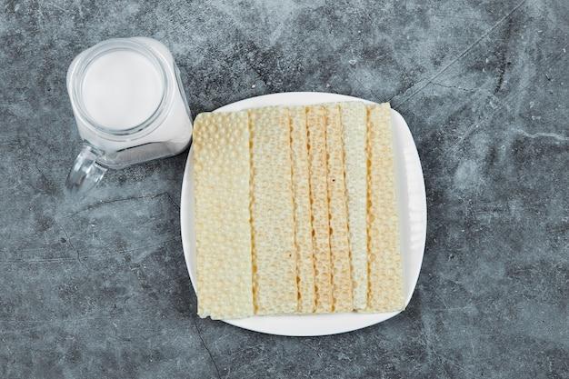 Um prato de biscoitos com leite.