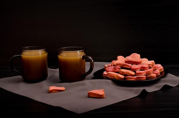 Um prato de biscoitos com vermelho em forma de coração, canecas de café com leite, dia dos namorados