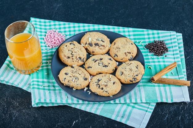 Um prato de biscoitos de chocolate e um copo de suco de laranja na mesa escura com canela