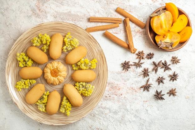 Um prato de biscoitos e paus de canela e anis estrelado e uma tigela de palmeira no chão de mármore