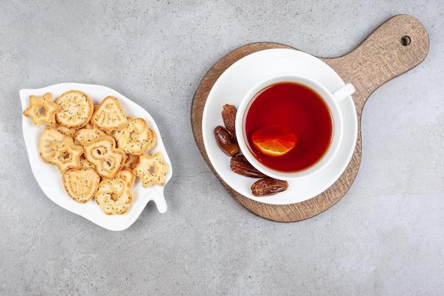 Um prato de biscoitos e uma xícara de chá com tâmaras no pires na placa de madeira na superfície de mármore.