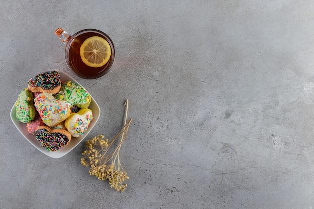 Um prato de biscoitos em forma de coração com granulado e uma xícara de chá quente