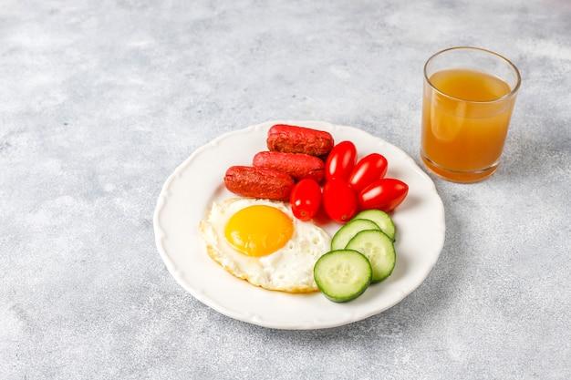 Um prato de café da manhã contendo linguiças de coquetel, ovos fritos, tomate cereja, doces, frutas e um copo de suco de pêssego.