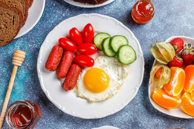 Um prato de café da manhã contendo linguiças de coquetel, ovos fritos, tomates cereja, doces, frutas e um copo de suco de pêssego.