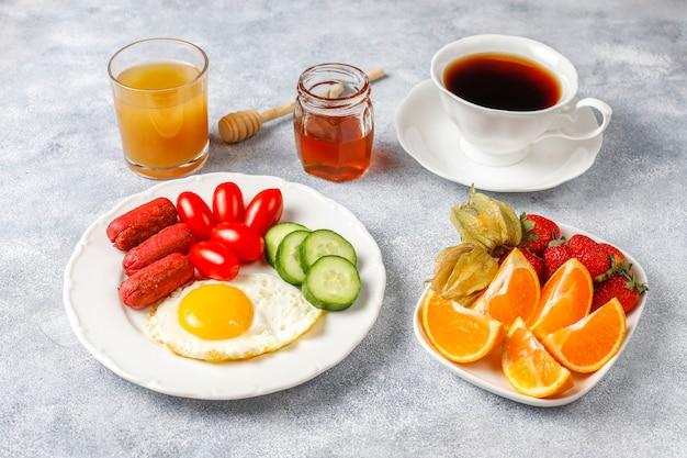 Um prato de café da manhã contendo linguiças, ovos fritos, tomate cereja, doces, frutas e um copo de suco de pêssego.