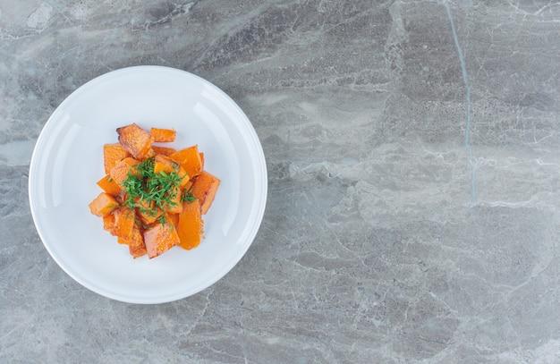 Um prato de cenouras fatiadas, na mesa de mármore.