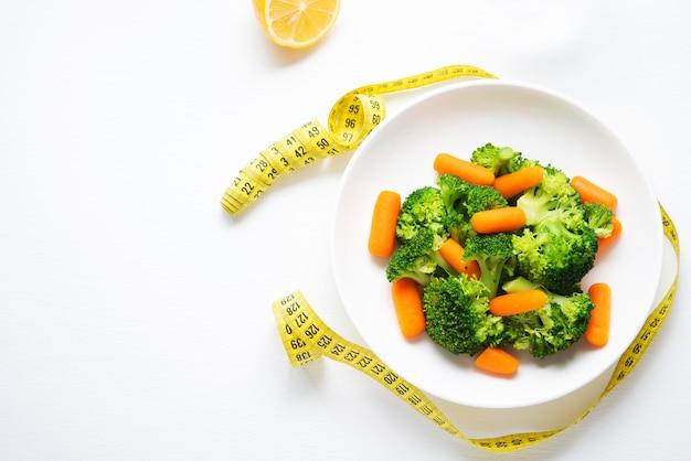 Um prato de comida dietética, vegetais cozidos, brócolis e cenoura, nutrição para exercícios físicos, cópia espaço, vista superior