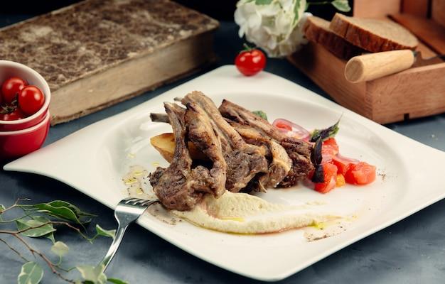 Um prato de costela de cordeiro grelhada com purê e batata frita