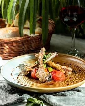 Um prato de costelas de cordeiro, servido com rúcula de tomate defumado e pimenta