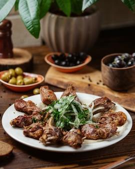 Um prato de costeleta de cordeiro entrecote kebab com cebola e verduras
