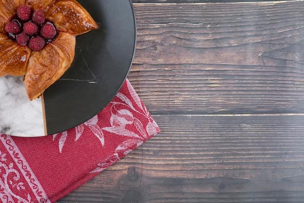 Um prato de deliciosa massa de framboesa colocado sobre uma mesa de madeira.