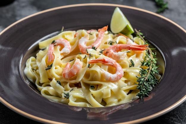 Um prato de delicioso camarão alfredo com alho e molho de natas sobre macarrão fettuccine. comida italiana, vista de cima. fundo de receita de comida. fechar-se.