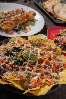 Um prato de deliciosos nachos de tortilla com molho de queijo derretido, carne picada, pimentão jalapeno, cebola roxa, cebola verde, tomate, azeitonas pretas, salsa e creme de leite com alegria de guacamole.