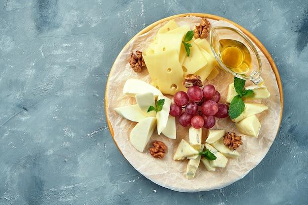 Um prato de diferentes queijos servido com uvas, nozes e mel. prato de queijo de aperitivo. camembert fatiado, brie, queijo azul parmesão