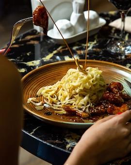 Um prato de fettuccine com camarão em molho teriyaki