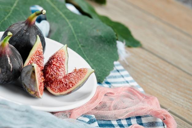 Um prato de figos pretos inteiros e fatiados com toalhas de mesa azuis e rosa na mesa de madeira.