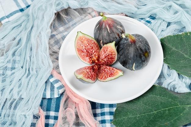 Um prato de figos pretos inteiros e fatiados com toalhas de mesa azuis e rosa.