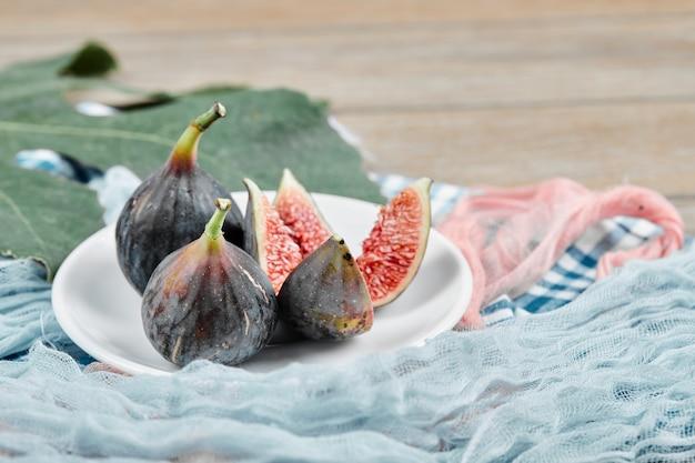 Um prato de figos pretos inteiros e fatiados, uma folha e toalhas de mesa azuis e rosa na mesa de madeira, close-up.